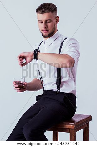 Studio Shot Elegant And Confident Man In Classical Wear Checking Time On Watches And Drinking Whiske