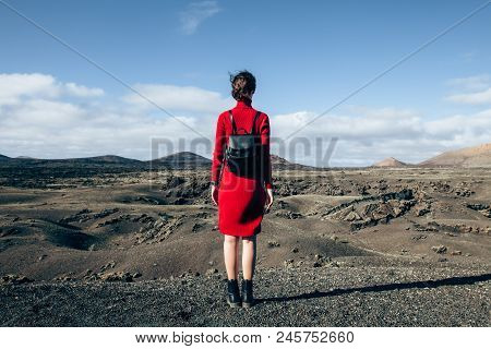 Back View Of Traveler Woman Enjoying Unique Volcanic Landscapes Of Timanfaya National Park, Lanzarot