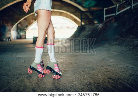 Well-built And Slim Legs Of Girl Are Pictured On Camera. She Is Standing On Her Toes. Rollers Are Gr