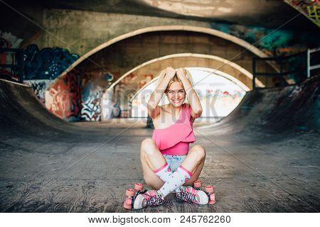 Gorgeous And Well-built Girl Is Sitting On The Ground And Looking Straight Forward On Camera. She Is