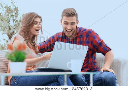 happy young couple watching a favorite movie while sitting in a modern living room.