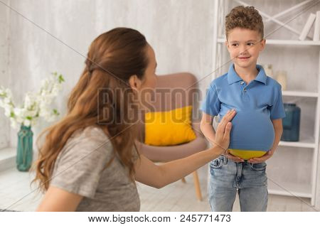 Family jokes. Cute curly haired little boy feeling rather amusing while joking with his dark-haired pregnant mother poster