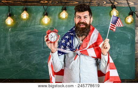 American Teacher With American Flags Holds Alarm Clock. Man With Beard On Cheerful Face Holds Flag O