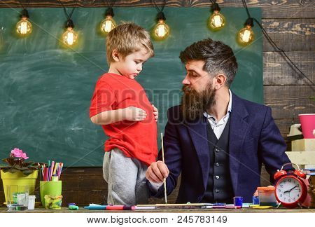 Fatherhood Concept. Teacher With Beard, Father Teaches Little Son To Draw In Classroom, Chalkboard O