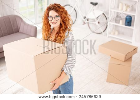 Start Of Life. Happy Vigorous Woman Smiling To Camera And Carrying Box