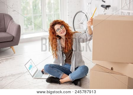 Total Order. Enthusiastic Energetic Woman Sitting On Floor And Rising Pencil