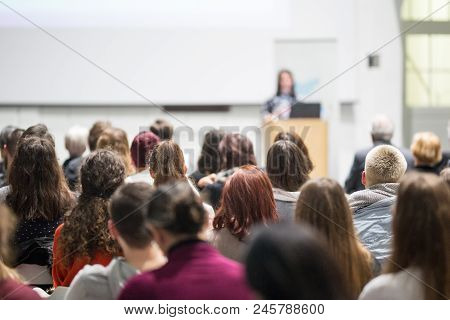 Female Speaker Giving Presentation In Lecture Hall At University Workshop. Audience In Conference Ha