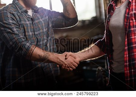 Cropped Shot Of Carpenter With Tattooed Hand Shaking Hand Of Partner At Sawmill
