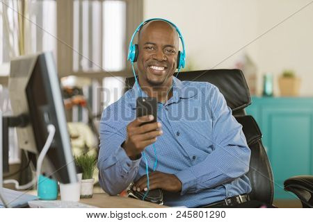 Relaxed Man In A Creative Office Listening To Music Or Other Media