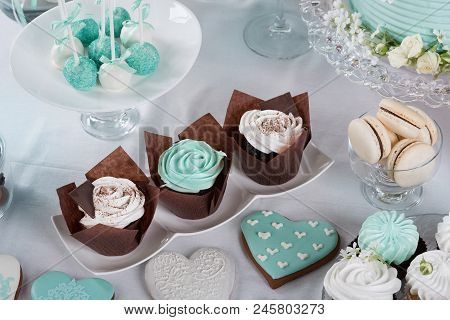 three cakes surrounded by gingerbread, sweets and other sweets on the festive table, candy bar for the wedding, selective focusing poster