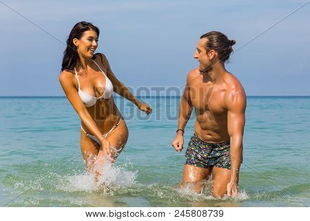 Happy Couple Laughing Together Holding Hands Running Having Fun Splashing Water In The Ocean Waves.