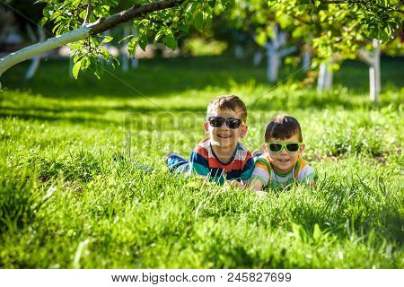 Happy Smiling Boy Sibling Brother Relaxing On The Grass. Close Up View With Copy Space.