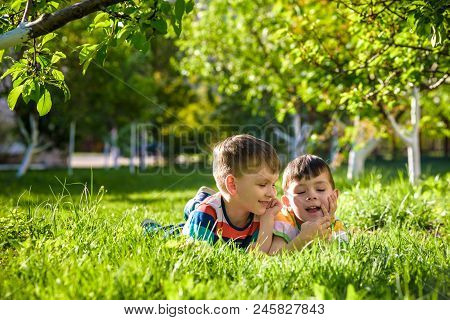 Happy Children Having Fun Outdoors. Kids Playing In Summer Park. Little Boy And His Brother Laying O