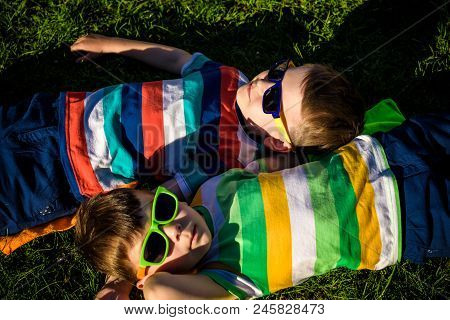 Happy Cheerful Smiling Children, Laying On A Grass, Wearing Sunglasses, Smiling At The Camera, Shot