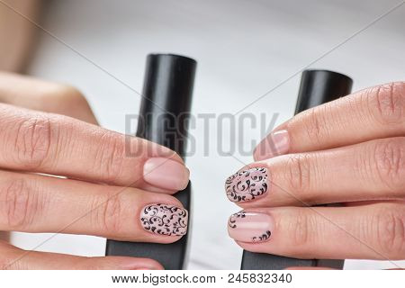 Female nails trendy art design. Womans hands with varnished nails holding bottles of nail polish. Beauty salon and spa. poster