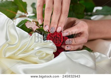 Female Hands With Red Roses On Silk. Young Womans Hands Holding Red Roses On White Silk. Concept Of