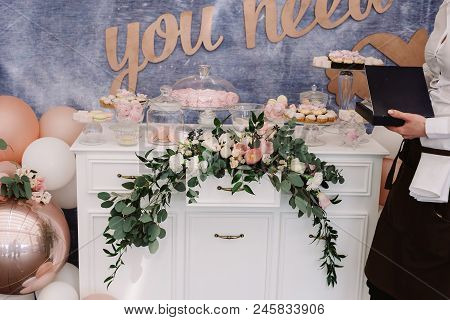 Beautiful sweets on a dresser. Stylish candy bar at a modern wedding. Candies, pastries, cakes stand on a dresser poster