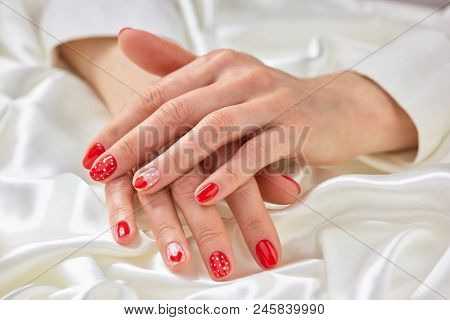Female Well-groomed Hands On Silk. Womans Hands With Beautiful Romantic Manicure On White Silk Mater