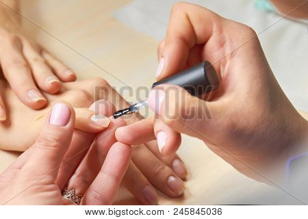 Manicurist Applying Colorless Varnish. Female Hands Applying Transparent Nail Polish On Healthy Nail