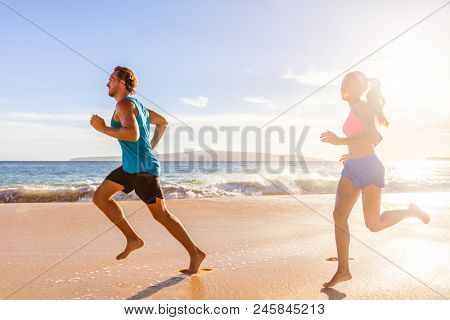 Jogging couple morning beach run healthy lifestyle. Active people training cardio workout together running barefoot in summer outdoors.