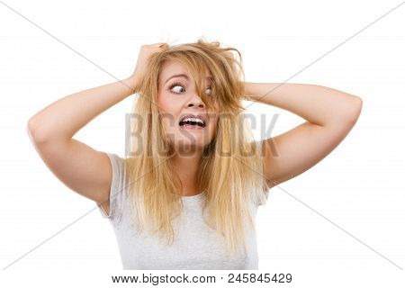 Bad Hairstyle Concept. Crazy, Mad Blonde Woman With Messy Hair Looking Stressed Out. Studio Shot On