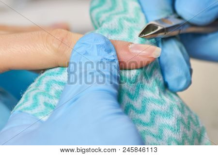 Beautician In Gloves Cutting Cuticle To Client. Beautician Trimming Cuticles Of Female Client. Manic