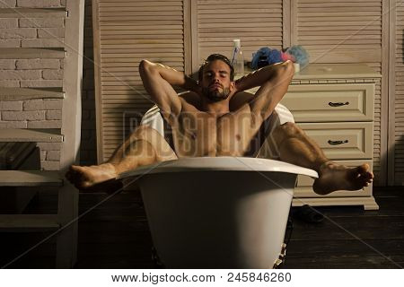 Man Relaxing In Spa Bath. Bodycare, Wellness, Pleasure, Relax. Man With Muscular Legs, Chest, Arms,