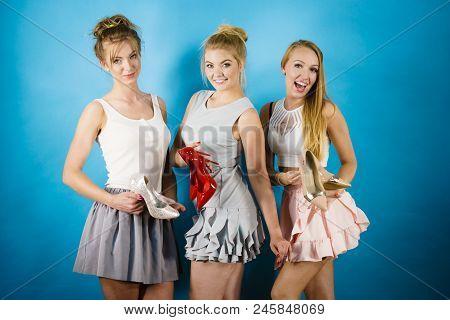 Three Gorgeous Women Fashion Stylist Presenting Stylish Shoes. Sensual High Heels Presentation. Outf