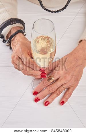 Woman Hands With Champagne Glass. Well-groomed Female Hands And Crystal Glass Of Champagne. Senior W