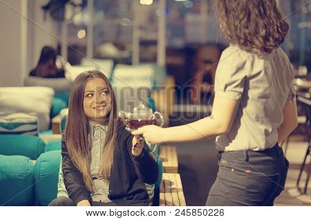 The Waitress Gives The Tea. A Hospitable Waitress Girl Gives A Tea And Tea Teapot For The Client In
