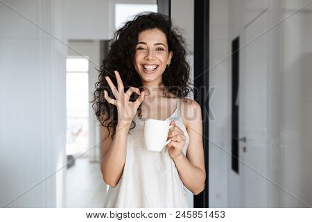 Portrait of caucasian curly woman with long dark hair smiling at camera, and showing ok sign while drinking tea at hotel apartment or flat in morning