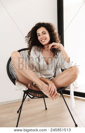 Full length photo of gorgeous woman 20s with long dark hair wearing silk leisure clothing smiling while sitting in chair at cozy flat poster