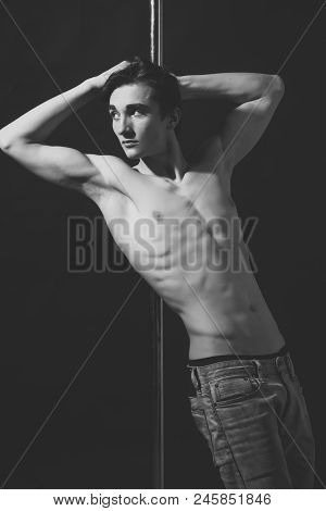 Thin, Taut Man. Young Strong Pole Dance Man With Nude Torso Lean On Metallic Pole. Shirtless Man Pol