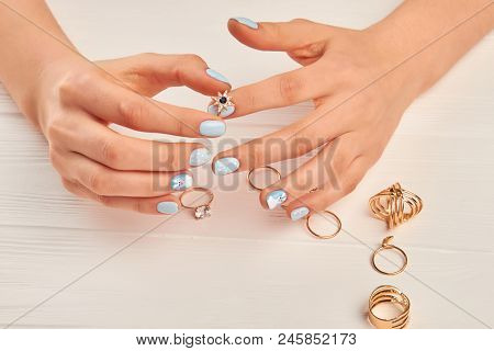 Female Hands Holding Ring With Stone. Female Hands With Beautiful Manicure And Many Golden Rings On