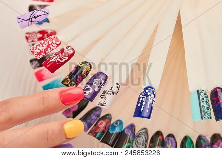 Female Finger Choosing Purple Nail Color. Nail Polish Testers With Different Design And Colors.