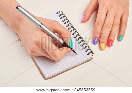 Writing Female Hand With Perfect Summer Manicure. Female Hand With Stylish Colorful Nails Holding Pe