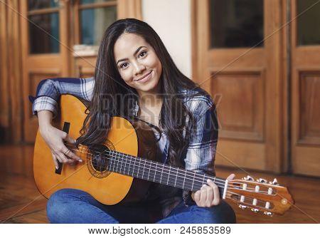 Portrait Of Beautiful Hispanic Woman Paying Acoustic Guitar Indoors