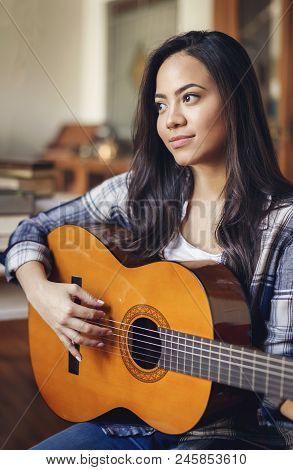 Portrait Of Beautiful Hispanic Woman Playing Acoustic Guitar