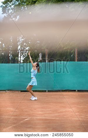 Gorgeous Girl Plays Tennis On The Court Outdoors. She Prepares To Beat Off A Ball. Woman Wears A Lig