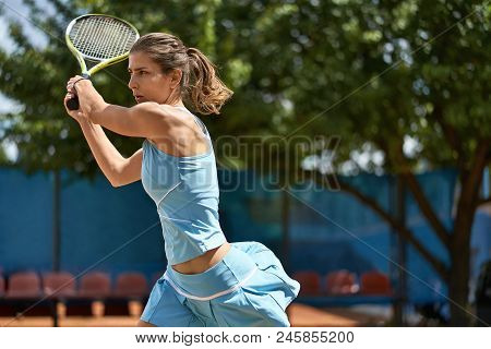 Amazing Girl Plays Tennis On The Court Outdoors. She Prepares To Beat Off A Ball. Woman Wears A Ligh