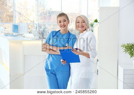 Female receptionist with trainee in hospital