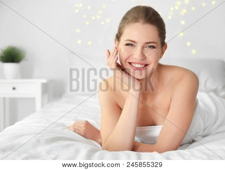 Young woman applying cream onto her skin indoors