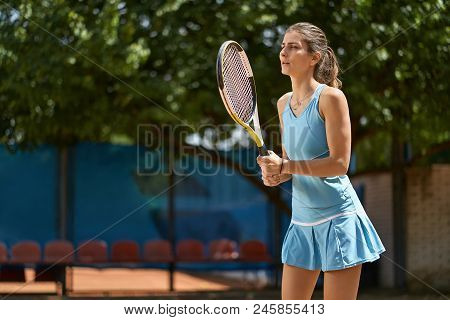 Young Girl Plays Tennis On The Court Outdoors. She Stands With A Racket In The Hands. Woman Wears A