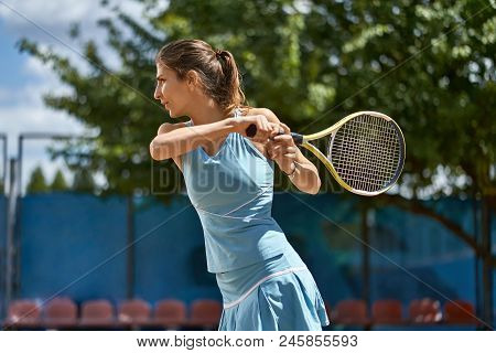 Nice Girl Plays Tennis On The Court Outdoors. She Prepares To Beat Off A Ball. Woman Wears A Light B