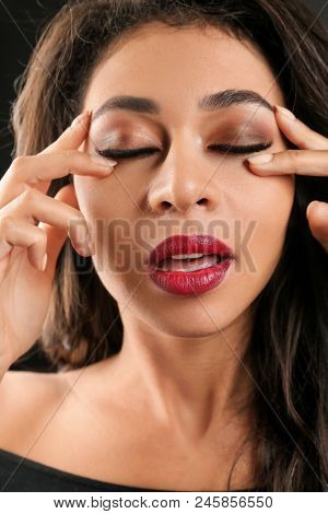 Attractive African-American woman with long eyelashes on black background. Eyelash extensions