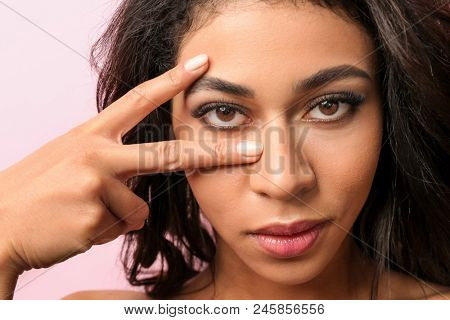 Attractive African-American woman with long eyelashes on color background. Eyelash extensions