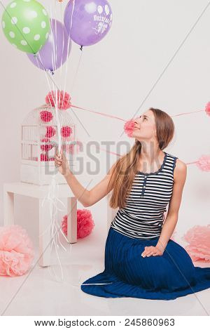 The Blonde Smiles And Looks At The Camera Between The Colored Balls On A White Background. Studio Po