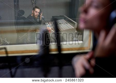 Sound Producer Listening To Girl Singing While Sitting At Console In Modern Sound Studio.