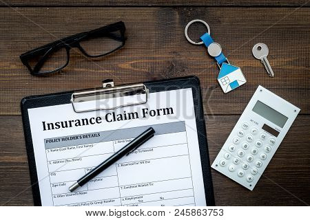 Real Estate Insurance. Insurance Claim Form Near House Keychain On Dark Wooden Background Top View.