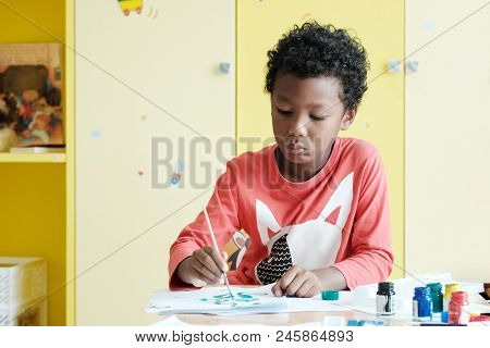 African Boy Painting In Classroom With Unhappy Emotion, Kid Education, Kindergarten Classroom Concep